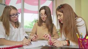 Muchachas adolescentes preciosas que estudian junto en la sala de clase, escribiendo en libro de texto metrajes