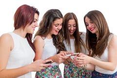 Muchachas adolescentes que comparten la información sobre los teléfonos elegantes Imagenes de archivo
