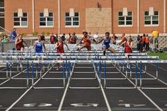 Muchachas adolescentes que compiten en carrera de vallas de la High School secundaria Imagen de archivo libre de regalías