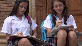 Muchachas adolescentes que escriben en la escuela almacen de video