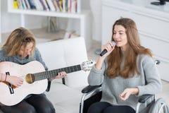 2 muchachas adolescentes que hacen la música junta una inhabilitada Imagen de archivo