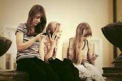 Muchachas adolescentes que invitan a los teléfonos celulares al aire libre Fotos de archivo