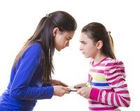 Muchachas adolescentes que luchan para la tableta digital Imagen de archivo libre de regalías