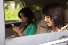 Muchachas adolescentes que mandan un SMS en el asiento trasero Fotografía de archivo