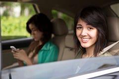 Muchachas adolescentes que mandan un SMS en el asiento trasero Imagen de archivo