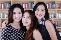 Muchachas adolescentes que se colocan en la biblioteca Foto de archivo libre de regalías