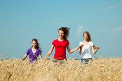 Muchachas adolescentes que se ejecutan en el campo de trigo Foto de archivo libre de regalías