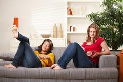 Muchachas adolescentes que se relajan en el sofá Imagenes de archivo