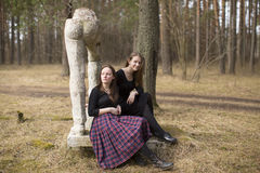Muchachas adolescentes que se sientan en la escultura quebrada en el parque Naturaleza Imagenes de archivo