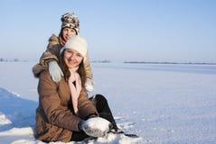 Muchachas adolescentes que se sientan en nieve Fotografía de archivo libre de regalías