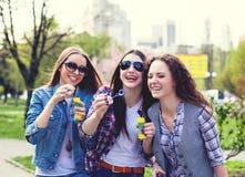 Muchachas adolescentes que soplan burbujas de jabón Adolescentes felices jovenes que se divierten en parque del verano Foto de archivo libre de regalías