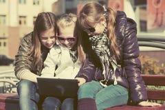 Muchachas adolescentes que usan el ordenador portátil en el banco Fotos de archivo