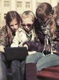 Muchachas adolescentes que usan el ordenador portátil en el banco Fotografía de archivo libre de regalías