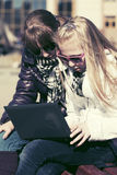 Muchachas adolescentes que usan el ordenador portátil en el banco Fotos de archivo libres de regalías