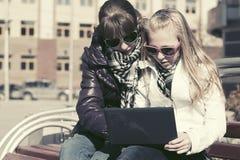 Muchachas adolescentes que usan el ordenador portátil en el banco Foto de archivo