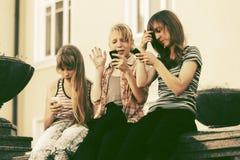 Muchachas adolescentes que usan los teléfonos elegantes contra una construcción de escuelas Fotos de archivo libres de regalías