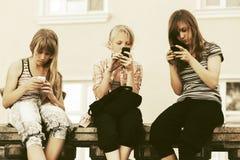 Muchachas adolescentes que usan los teléfonos elegantes contra una construcción de escuelas Foto de archivo libre de regalías