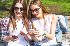 Muchachas adolescentes que usan sus teléfonos Adolescentes felices jovenes que se divierten en parque del verano Imagen de archivo