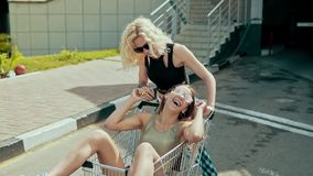 Muchachas adolescentes sonrientes del inconformista que se divierten en carro de la compra en el estacionamiento almacen de video