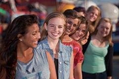 Muchachas adolescentes sonrientes en línea Imagen de archivo