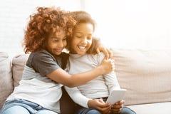 Muchachas afroamericanas que usan el tiempo del smartphone y del gasto junto fotos de archivo libres de regalías