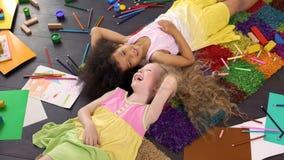 Muchachas afroamericanas y caucásicas que mienten en la alfombra y que ríen, niñez feliz foto de archivo