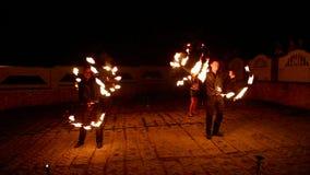 Muchachas agraciadas y muchachos que bailan danza apasionada con la fan del fuego en su mano Encienda la demostración metrajes