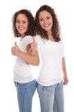Muchachas aisladas sonrientes con los pulgares para arriba: gemelos reales Foto de archivo libre de regalías