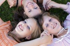 Muchachas alegres de los amigos que ponen en hierba junto Foto de archivo