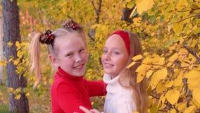 Muchachas alegres del adolescente que ríen y que bailan junto en parque del otoño almacen de metraje de vídeo