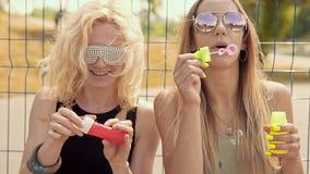 Muchachas alegres del inconformista en las gafas de sol que se divierten que hace burbujas al aire libre almacen de video