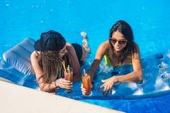 Muchachas alegres que beben los cócteles en la piscina Fotografía de archivo