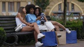 Muchachas alegres que comparten el teléfono móvil en el banco almacen de metraje de vídeo