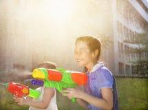 Muchachas alegres que juegan los armas de agua en el parque Imagen de archivo