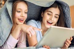 Muchachas alegres que miran el vídeo debajo de la manta Fotografía de archivo