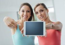Muchachas alegres que muestran una tableta Fotos de archivo