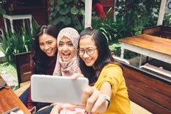 Muchachas amistosas que hacen el selfie en café Imagenes de archivo