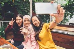 Muchachas amistosas que hacen el selfie en café Imagen de archivo libre de regalías