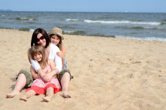 Muchachas amontonadas en la playa asoleada Imagenes de archivo