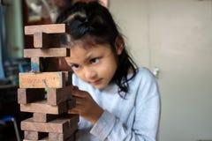 Muchachas asiáticas que juegan el jenga, los juegos de madera de los bloques de la habilidad física Imagen de archivo libre de regalías