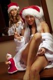 Muchachas atractivas en los sombreros de Santa que esperan Año Nuevo Foto de archivo