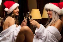 Muchachas atractivas en los sombreros de Santa que esperan Año Nuevo Imágenes de archivo libres de regalías