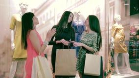 Muchachas atractivas que se colocan en alameda de compras y que hablan el uno al otro almacen de metraje de vídeo
