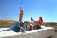 Muchachas aventureras en convertible Imagen de archivo libre de regalías