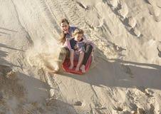 Muchachas aventureras que suben abajo de las dunas de arena Foto de archivo libre de regalías