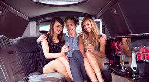 Muchachas bonitas con el hombre de las señoras en la limusina Foto de archivo libre de regalías