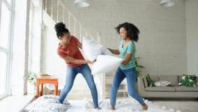 Muchachas bonitas jovenes de la raza mixta que saltan en las almohadas de la cama y de la lucha que se divierten en casa Imagen de archivo libre de regalías