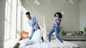Muchachas bonitas jovenes de la raza mixta que saltan en las almohadas de la cama y de la lucha que se divierten en casa Fotografía de archivo