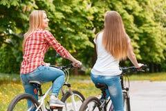 Muchachas bonitas que presentan con las bicis en parque Imagen de archivo libre de regalías