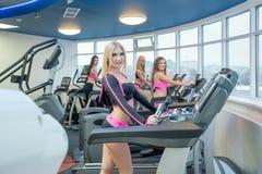 Muchachas bonitas que presentan mientras que ejercita en el gimnasio Fotografía de archivo